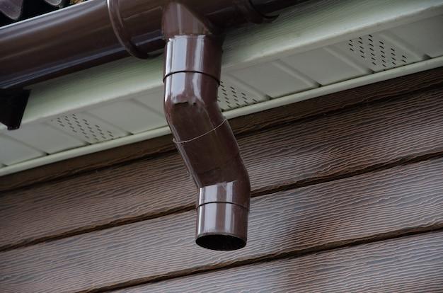 Grondaia con pluviale sul tetto di una casa.