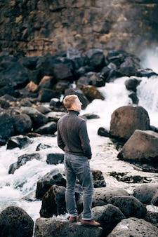 Un ragazzo con un maglione lavorato a maglia nero si erge sulle rocce vicino alle cascate ehsaraurfoss ehsarau river national park