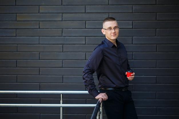 Il ragazzo con la camicia nera sta bevendo il caffè da un bicchiere di carta rosso.
