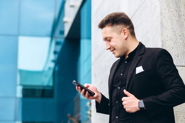 Il ragazzo con l'abito nero del moderno business center di vetro.