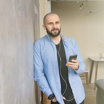 Un ragazzo in camicia blu e jeans neri sta parlando al telefono con le cuffie