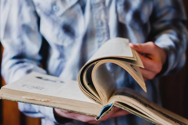 Un ragazzo con una camicia blu sfoglia le pagine di un vecchio libro contro la biblioteca. lo studente cerca di acquisire nuove conoscenze. concetto per la giornata mondiale del libro