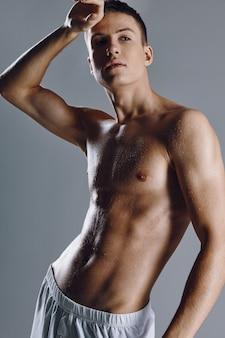 Ragazzo bodybuilder con pompato i muscoli del braccio su sfondo grigio vista ritagliata close-up.