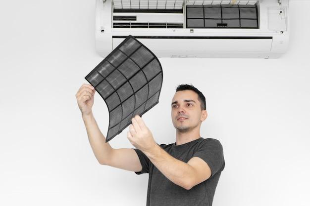 Il ragazzo pulisce il filtro del condizionatore d'aria di casa dalla polvere.