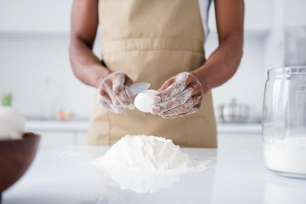 Ragazzo pasticcere che fa pane fresco e morbido che impasta le uova di farina culinaria nella moderna cucina interna