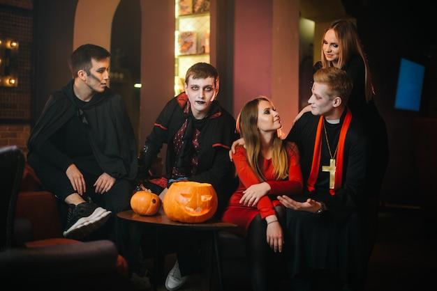 Il ragazzo con il costume di halloween del conte dracula è seduto con gli amici in un bar e guarda la telecamera
