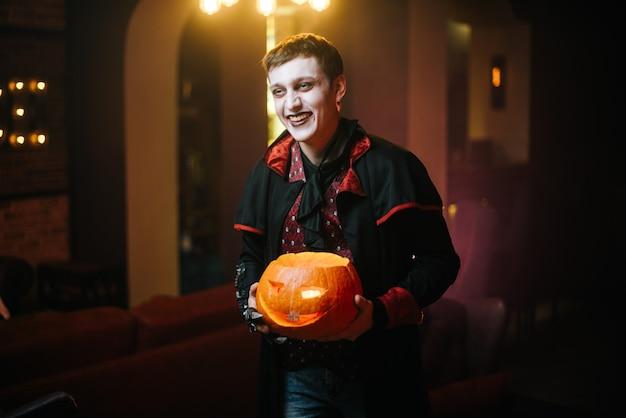 Il ragazzo con il costume di halloween del conte dracula che ride tiene in mano una zucca natalizia intagliata.