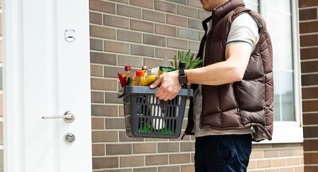 Il ragazzo consegna il cesto pieno di generi alimentari alla porta di casa. acquisti online.