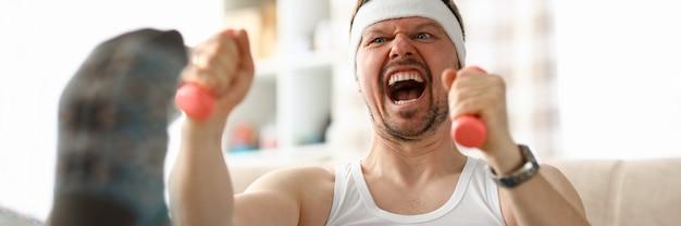 Ragazzo facendo esercizi con manubri in mano. includi fitness nel tuo programma. Foto Premium
