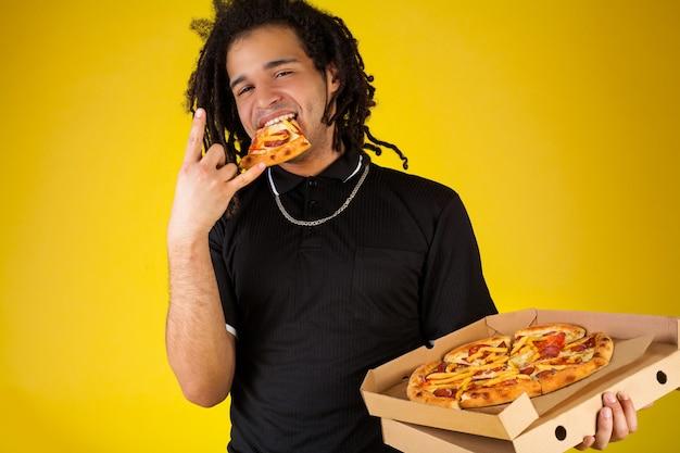 Il ragazzo mangia la pizza e sorride su un giallo