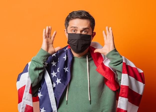 Ragazzo in maschera e felpa con cappuccio verde con bandiera usa sull'arancio