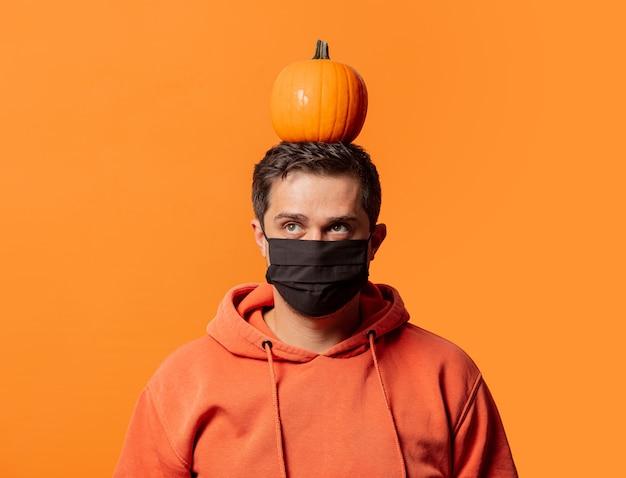 Ragazzo in maschera con la zucca in testa sull'arancio
