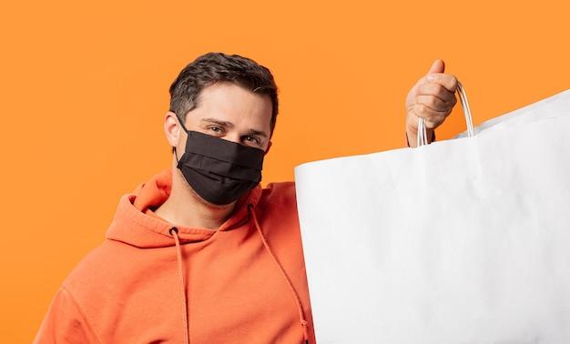Ragazzo in maschera e con le borse della spesa sull'arancia