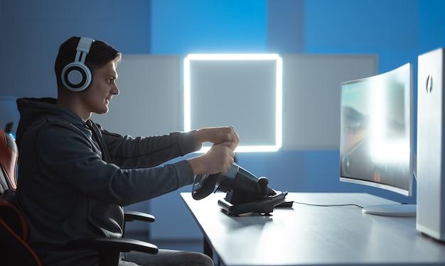 Il giocatore con l'auricolare che gioca ai videogiochi sul suo personal computer