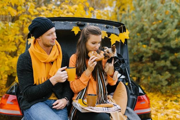 Un ragazzo e una ragazza sono seduti nel bagagliaio aperto di un'auto con il loro cane