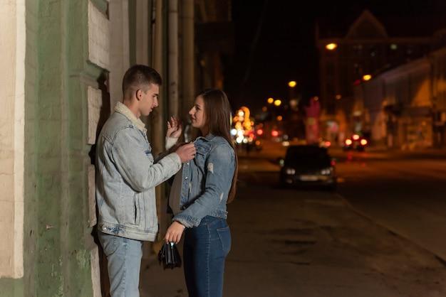 Ragazzo e ragazza discutono a tarda notte in città. guy è desideroso di abbracciare la sua ragazza. appuntamento serale. appuntamento romantico.