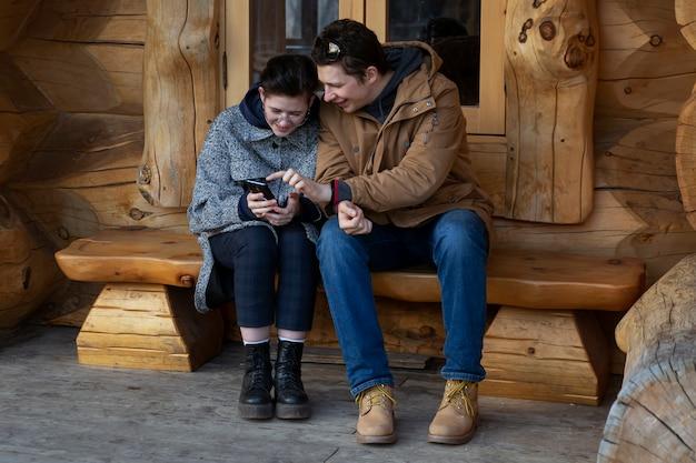 Il ragazzo e la ragazza si divertono a parlare e a guardare lo schermo dello smartphone comunicazione