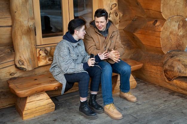Il ragazzo e la ragazza si divertono a parlare seduti su una panchina vicino a una bella casa di legno