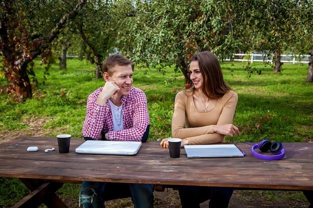 Un ragazzo e una ragazza si siedono a un tavolo di legno nel parco e lavorano su laptop con le cuffie f