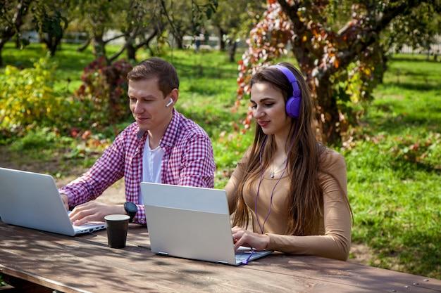 Un ragazzo e una ragazza si siedono a un tavolo di legno nel parco e lavorano su laptop con le cuffie