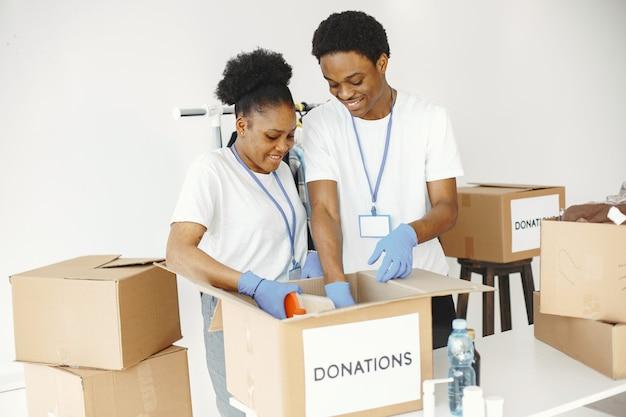 Ragazzo e ragazza volontari. amici in magliette bianche. aiuti umanitari ai poveri.