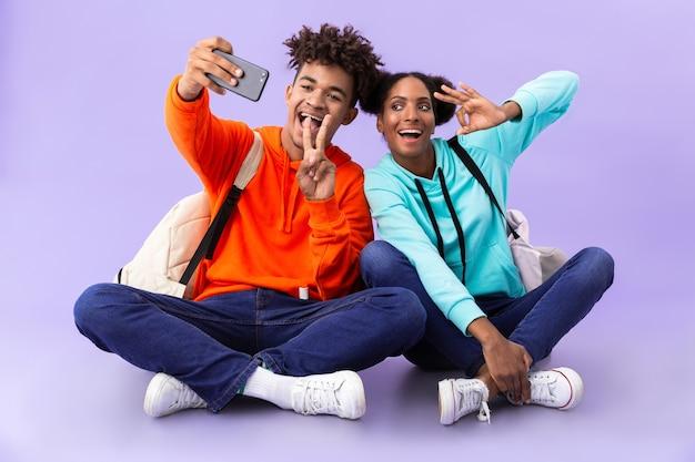 Ragazzo e ragazza che indossano zaini che scattano foto selfie mentre era seduto sul pavimento con le gambe incrociate, isolato sopra il muro viola