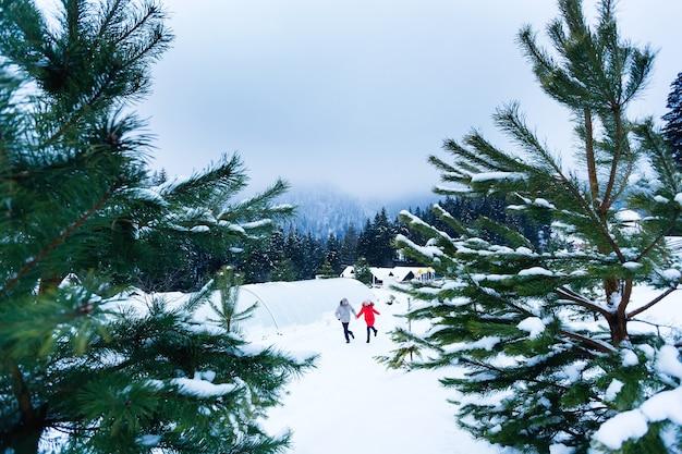Ragazzo e ragazza in abiti invernali si tengono per mano e corrono intorno a un edificio in legno tra le montagne e gli alberi di conifere