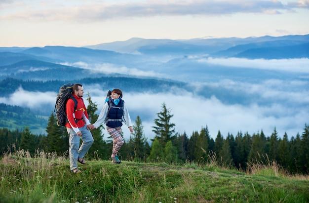 Il ragazzo e la ragazza con gli zaini sono su un sentiero di montagna che si divertono