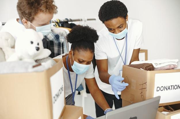 Ragazzo e ragazza con caselle di controllo volontari in maschere con laptop scatole con aiuti umanitari