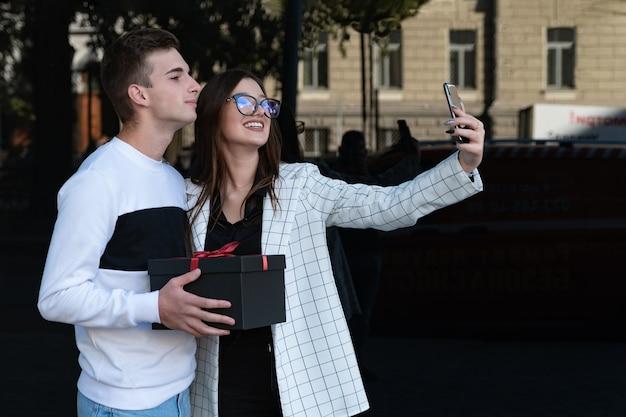 Il ragazzo fa un regalo alla sua ragazza. la donna felice fa il selfie con il suo ragazzo. sorridente coppia innamorata.