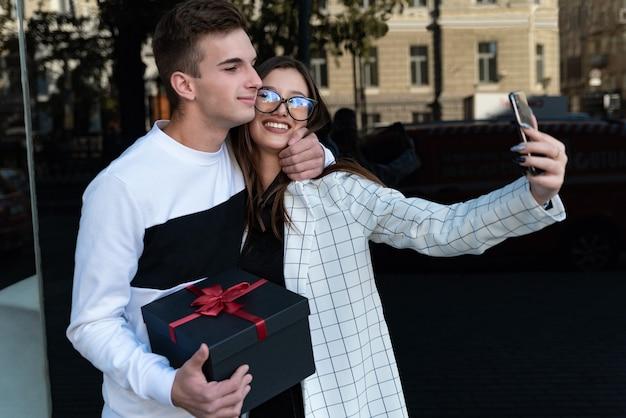 Guy fa un regalo alla sua ragazza e la abbraccia. la coppia felice innamorata del regalo nelle loro mani fa selfie. sorridente coppia innamorata.