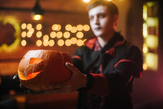 Il tipo in costume di halloween del conte dracula tiene in mano una zucca intagliata. volto sfocato di un uomo sullo sfondo