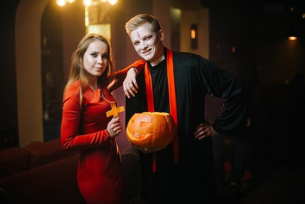 Un tipo in costume da prete di halloween tiene in mano una zucca intagliata. una ragazza con un vestito rosso guarda la telecamera con un giovane