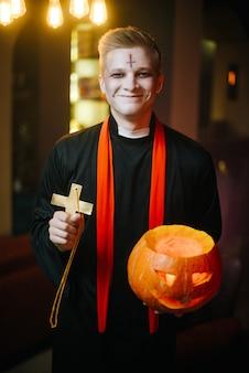 Un tipo in costume da prete di halloween tiene in mano una zucca intagliata e sorride. l'altra mano alza una croce religiosa. il giovane esamina la macchina fotografica.