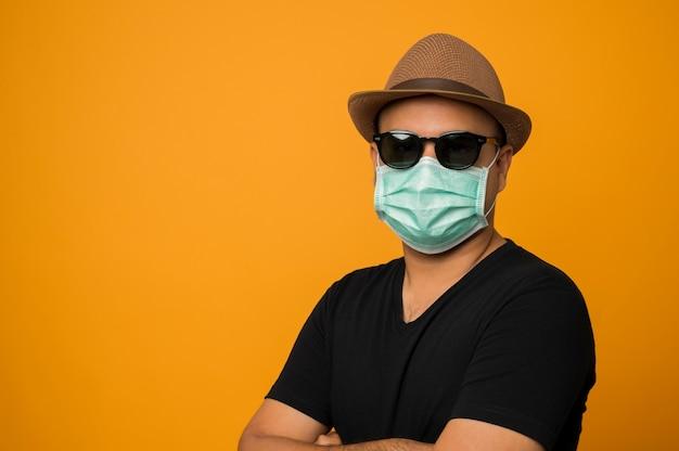 Ragazzo in cappello che indossa la maschera per il viso messo su occhiali da sole