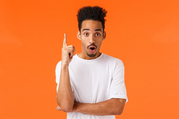 Guy ha una grande idea. attraente giovane studente di college afro-americano alzare il dito indice nel gesto di eureka, dicendo il suo piano, trovato la soluzione, rispondere alla domanda, suggerire risolvere, arancione