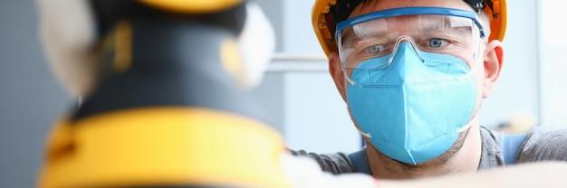 Ragazzo in un casco e occhiali di sicurezza con una levigatrice