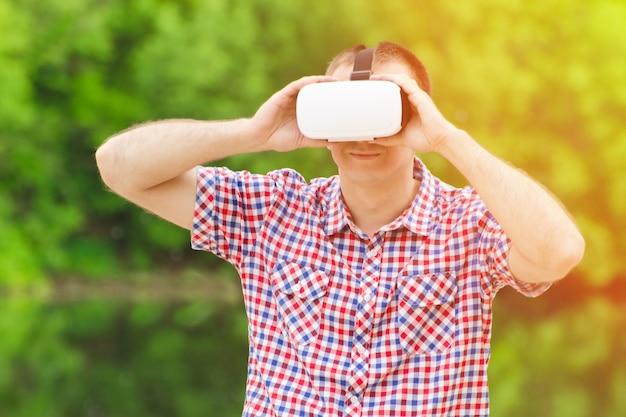 Ragazzo nel casco della realtà virtuale sullo sfondo della natura
