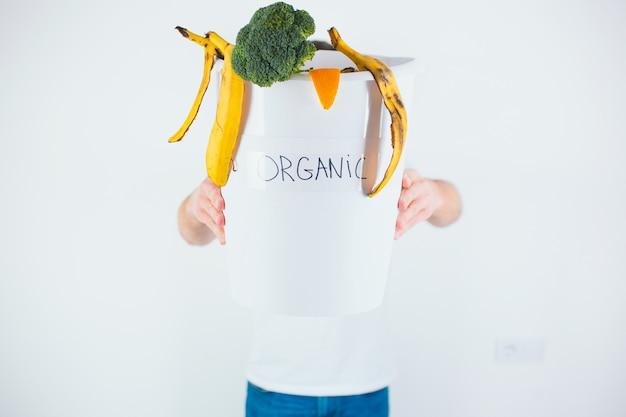Ragazzo tiene il secchio con rifiuti organici all'interno di se stesso