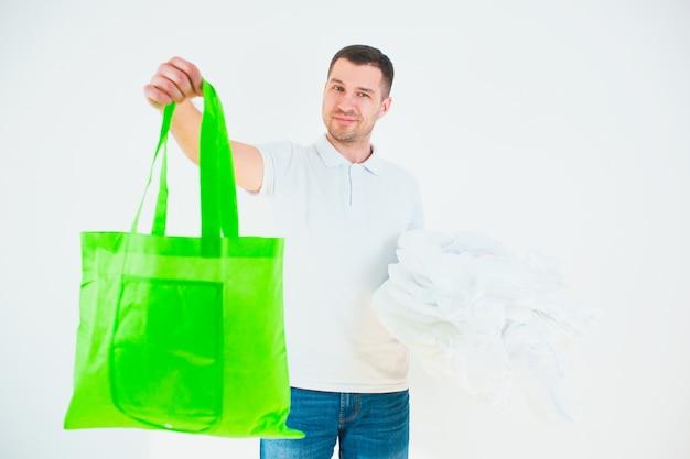 Guy tiene in mano una borsa ecologica verde e un'altra in buste di plastica bianca. stile di vita senza sprechi.