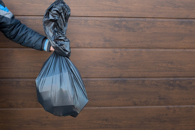 Il ragazzo tiene un primo piano nero del sacchetto della spazzatura.