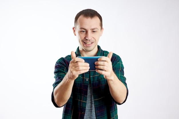Guy tiene il telefono tra le mani e lo indica con il dito. un uomo gioca sul suo telefono e guarda video, social network