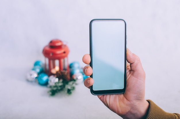 Il ragazzo tiene in mano uno smartphone con uno schermo bianco