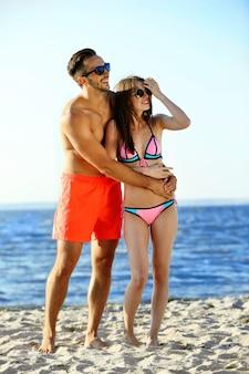 Un ragazzo che abbraccia una donna in spiaggia, all'aperto
