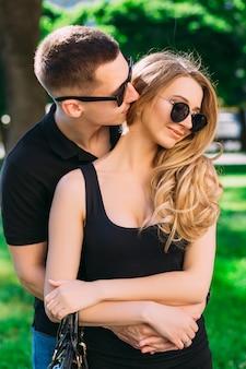 Il ragazzo abbraccia la ragazza dalla parte posteriore. ragazza bionda in occhiali da sole