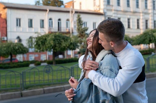 Guy abbraccia le spalle delle ragazze e la bacia. giovani coppie nell'amore che abbracciano all'aperto.