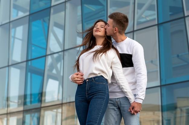 Guy abbraccia e bacia la sua ragazza per strada. giovane coppia innamorata. costruzione della città sullo sfondo.