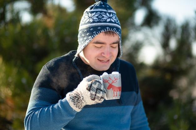 Il ragazzo sta bevendo una bevanda calda con marshmallow in inverno nella foresta. un'accogliente passeggiata invernale attraverso i boschi con una bevanda calda