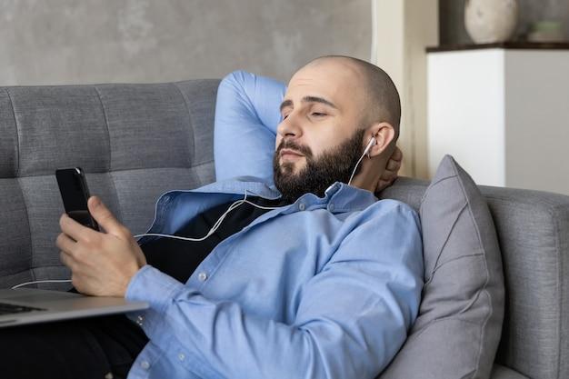 Il ragazzo è sdraiato sul divano e lavora su un laptop e parla al telefono. il concetto di lavorare da casa