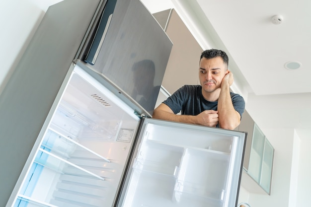 Il ragazzo è triste vicino al frigorifero vuoto